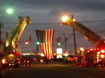 Two firetrucks and a flag